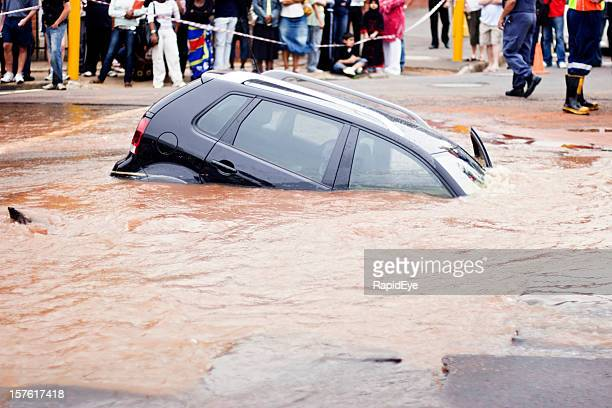 Car slips under muddy water in flooded street