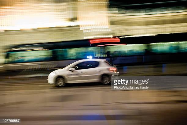 Car speeding down street at night