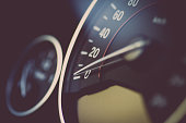 Close up shot of a speedometer in a car.