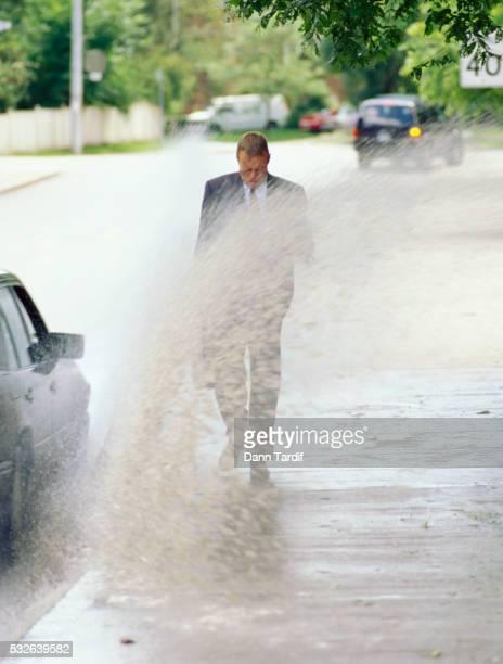 Car Splashing Water on Businessman