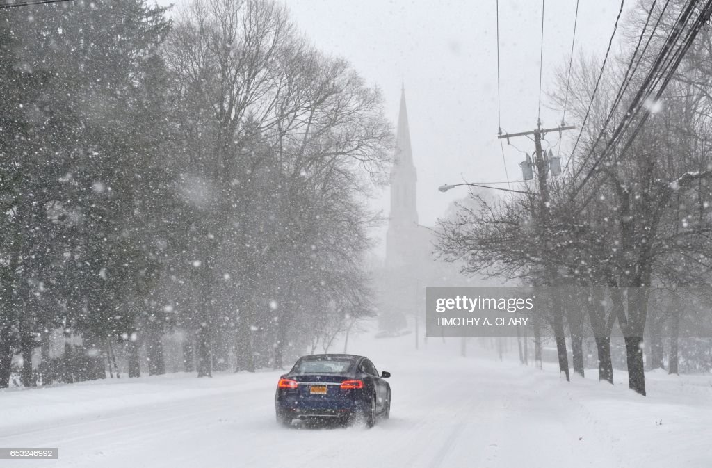 A car srives through a back street in a neighborhood in Greenwich, Connecticut March 14, 2017. Winter Storm Stella dumped snow and sleet Tuesday across the northeastern United States where thousands of flights were canceled and schools closed, but appeared less severe than initially forecast. After daybreak the National Weather Service (NWS) revised down its predicted snow accumulation, saying that the storm had moved across the coast. A. CLARY