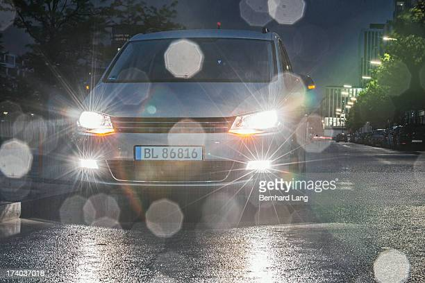 car standing on urban street, headlights on
