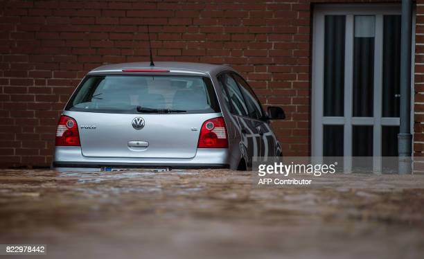 A car stands in an overflooded street in front of a house in Rhueden northern Germany on July 26 2017 Some parts of lower saxony are overflooded...