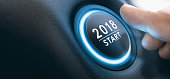 Finger pressing a 2018 start button. Concept of new year, two thousand eighteen. Composite between a photography and a 3D background. Horizontal image