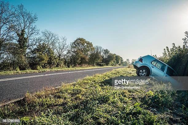 Car sticking out of hedge on rural highway roadside