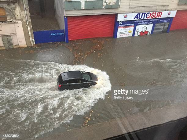 A car struggles through a flooded street on August 23 2015 in Nimes France Heavy rains caused flash flooding in the city in Southern France The image...