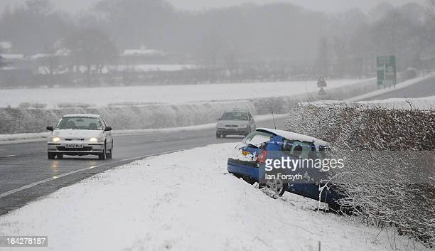 A car that had crashed into a hedge during heavy snow is marked with police tape as snow continues to fall on March 22 2013 in Harrogate United...