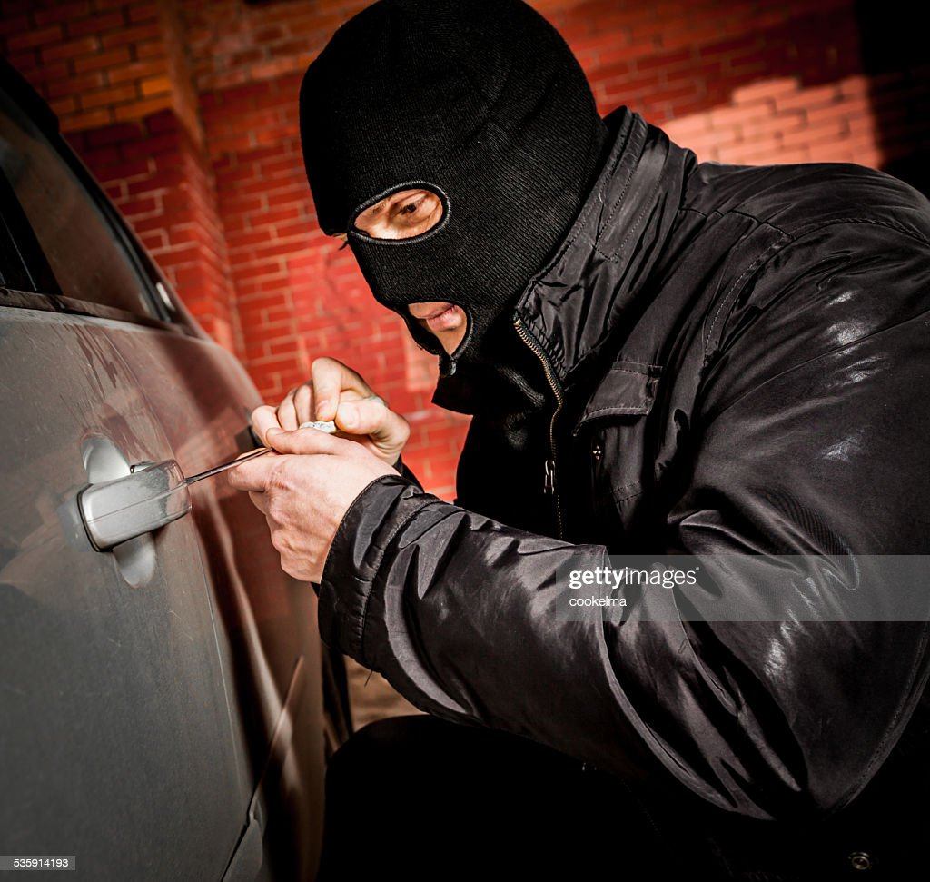 Car thief in a mask. : Stock Photo