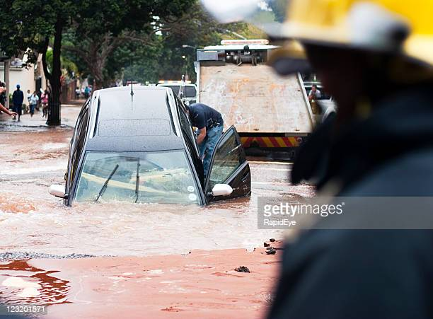 Car tips into pothole in flooded street, front view