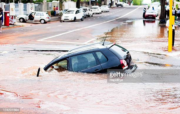 Car tips into pothole in flooded street, side view