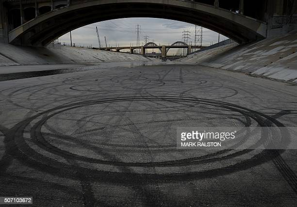 Car tire marks in the Los Angeles River after the closure of the iconic 6th Street Bridge that connects downtown Los Angeles with its eastern...