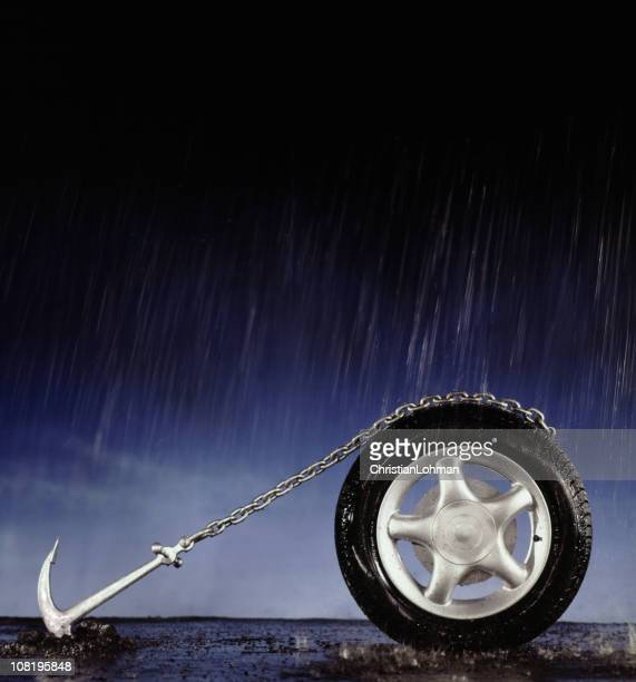 Car tire with chain anchored to the ground in the rain