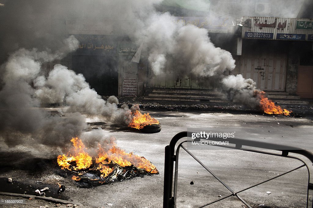 Car tires are seen on fire during clashes between Palestinian demonstrators and Israeli soldiers in Hebron April 3, 2013. Palestinians across the West Bank and Gaza were observing a general strike, with prisoners refusing food to mourn the death of a fellow inmate in an Israeli jail.