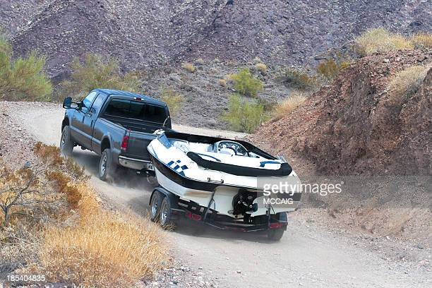 A car towing a boat through the dirt road