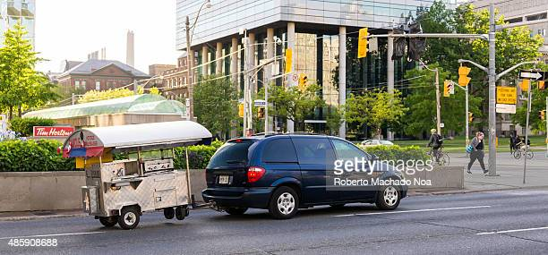 Car towing a mobile hotdog vending cart on the road in Toronto The car is transporting the mobile food cart to another place