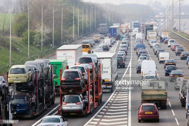 Car transporter lorries travelling among congested traffic on M1 motorway in Hertfordshire United Kingdom