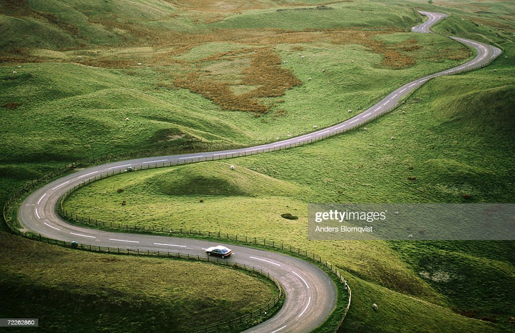 Car travelling down snaking road through grazing land of the Peak District, United Kingdom : Stock Photo