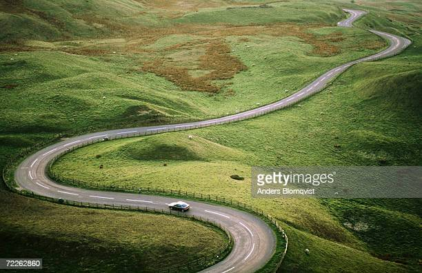 Car travelling down snaking road through grazing land of the Peak District, United Kingdom