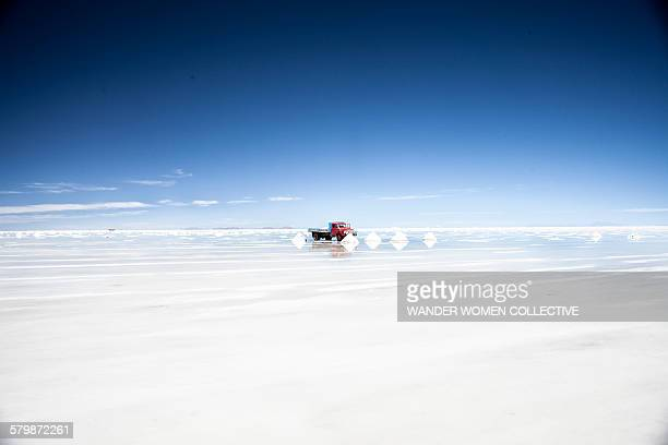 Car travelling on Uyuni Salt Flats Bolivia