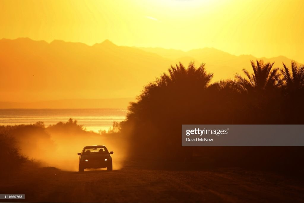 A car travels a dirt road in a date palm farm at sunrise in an area where a controversial development would create a new town for nearly 40,000 people on the northwest shore of the biggest lake in California, the Salton Sea, in the distance, on March 21, 2012 south of Mecca, California. The Center for Biological Diversity and the Sierra Club have filed a lawsuit against Riverside County after the Board of Supervisors approved a record-sized development project for Riverside County, saying that it would increase pollution and threaten wildlife in nearby parks at the Salton Sea and in the largest state park in California, Anza-Borrego Desert State Park. Though massive fish die-offs occur annually, drawings in the Travertine Point plans feature peaceful marinas but the lake has been plagued by dropping water levels and increasing salt levels for decades. Scientists say that a catastrophic decline in the fish population is inevitable and a resulting 25 to 50 percent drop in the migratory bird population will destroy a major stopping point in the Pacific bird migration route. The shrinking salt lake is exposing more and more fine dust, posing health problem as blows it across the region. Funding to stop the ecological collapse of the sea is not likely in the near futures with its $9 billion price tag.
