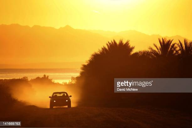 A car travels a dirt road in a date palm farm at sunrise in an area where a controversial development would create a new town for nearly 40000 people...
