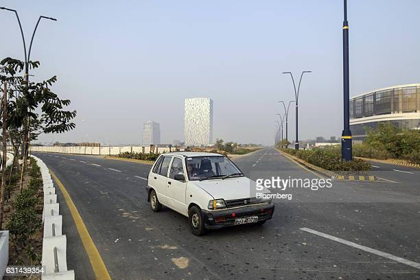 A car travels along a road as Gift Two tower center stands in the background in Gujarat International Finance TecCity Gujarat India on Monday Jan 9...