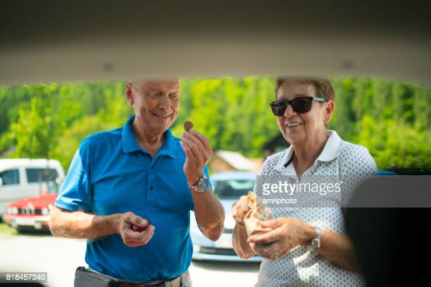 Car Trip, happy laughing active seniors at car on rest area