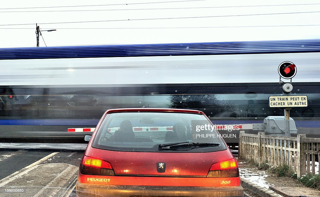 A car waits as a regional train (TER) passes at a level crossing in Fletre, northern France, on January 14, 2013. AFP PHOTO / PHILIPPE HUGUEN