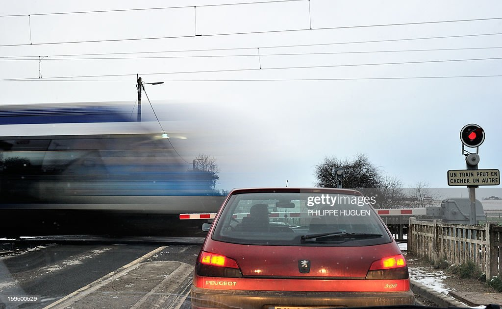 A car waits as a regional train (TER) passes at a level crossing in Fletre, northern France, on January 14, 2013.