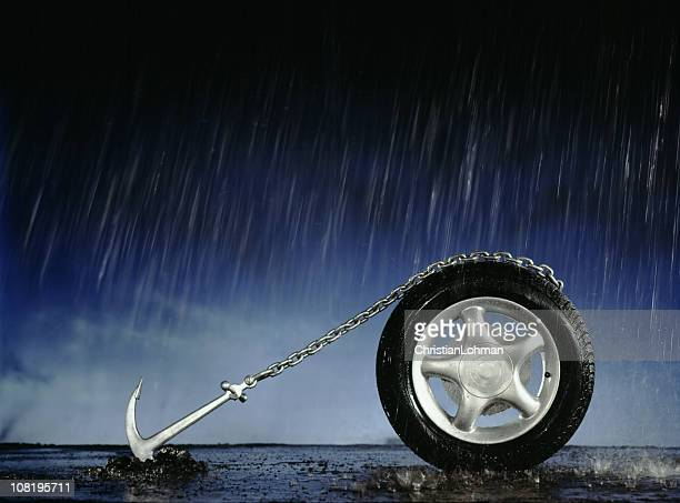 Car Wheel Anchored to Ground in Pouring Rain