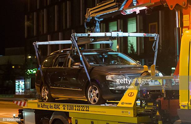 A car with broken glass gets transported off from the shooting area at the Olympia Einkaufzentrum shopping mall on July 22 2016 in Munich Germany...