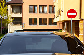 Car with dark tinted windows in an urban street below colorful apartment blocks and a no entry sign, close up view of the windshield