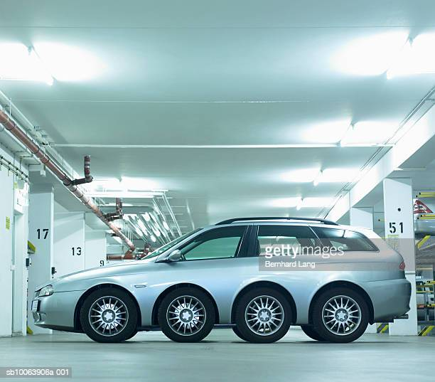 Car with eight wheels in garage, side view (digital composite)