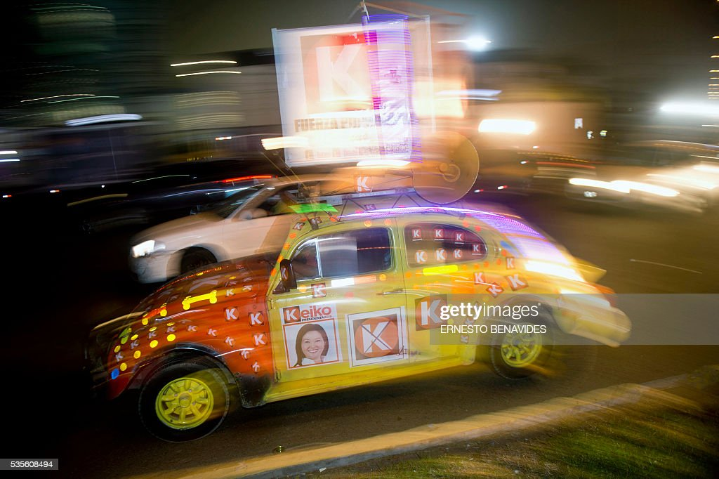 A car with posters of Peruvian presidential candidate for the Fuerza Popular (Popular Strength) party Keiko Fujimori is seen before a televised debate with Pedro Pablo Kuczynski of the 'Peruanos por el Kambio' (Peruvians for change) party in Lima on May 29, 2016. Fujimori and Kuczynski will compete in Peru's June 5 runoff election. / AFP / ERNESTO