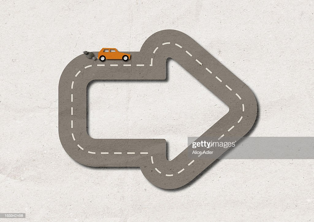 A car with smoke coming from exhaust driving on street shaped like an arrow : Stock Photo