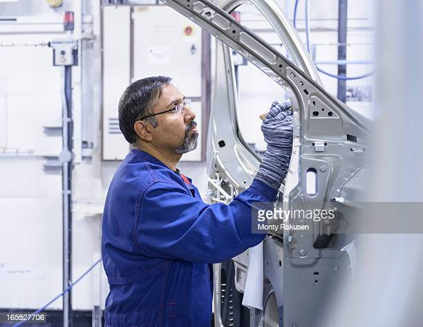 Car worker applying sealant to car body in car factory