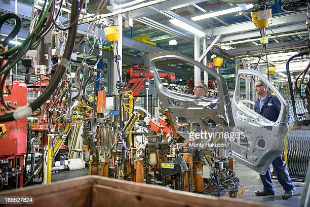 Car workers welding car doors in car plant