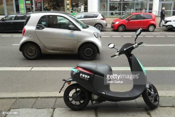 Car2Go drives past a parked Coup electric scooter in the city center on November 14 2017 in Berlin Germany A number of companies have plunged into...