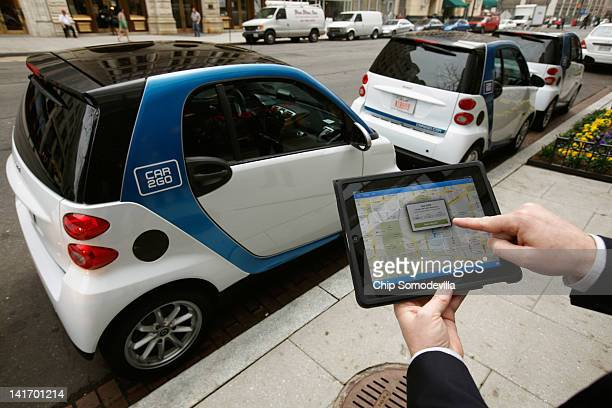 A car2go employee shows how members can use a smartphone or iPad app to locate and reservec car2go vehicles March 22 2012 in Washington DC Beginning...