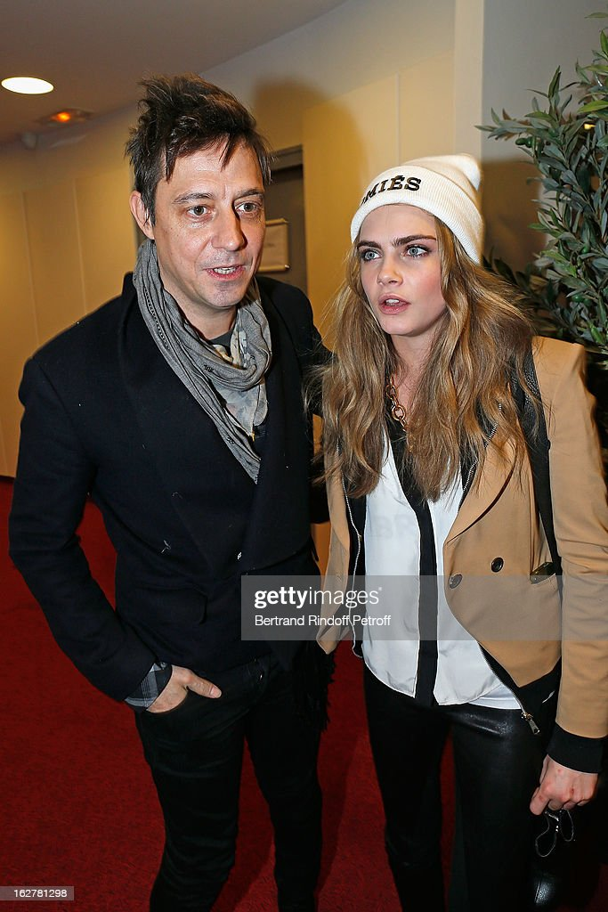 Cara Delevingne (R) and Jamie Hince pose backstage following the Etam Live Show Lingerie at Bourse du Commerce on February 26, 2013 in Paris, France.