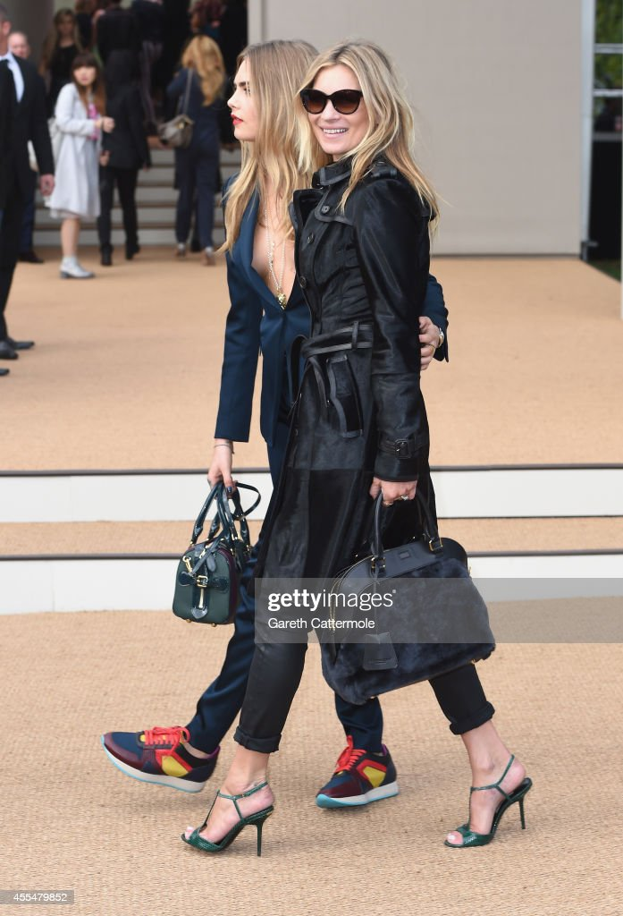 Cara Delevingne and Kate Moss attend the Burberry Womenswear SS15 show during London Fashion Week at Kensington Gardens on September 15, 2014 in London, England.