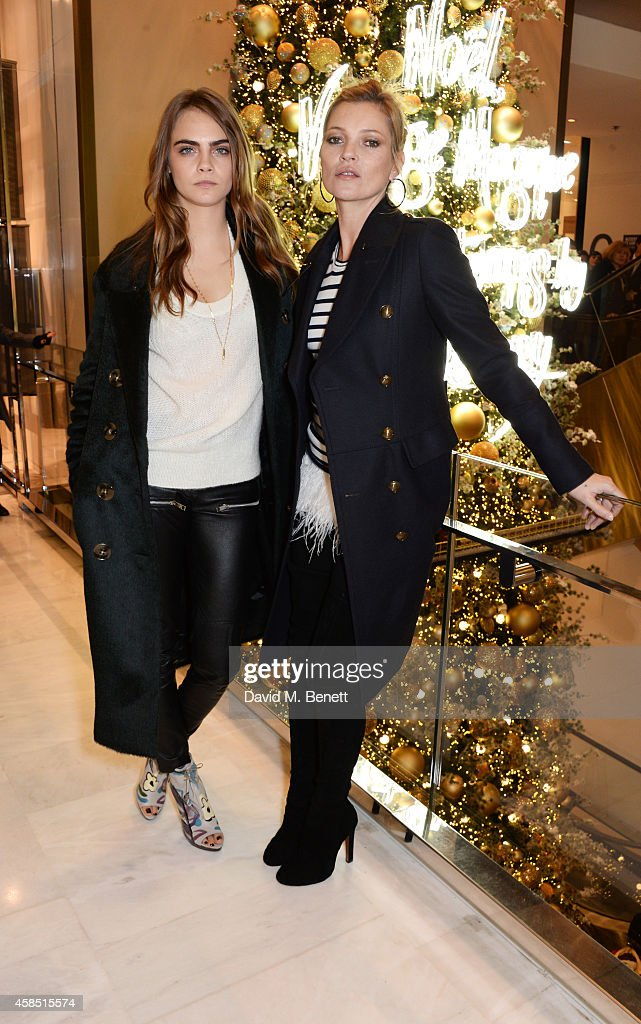 Cara Delevingne (L) and Kate Moss attend 'The Magical Christmas Journey By Burberry' Printemps Collaboration at Le Printemps on November 6, 2014 in Paris, France.