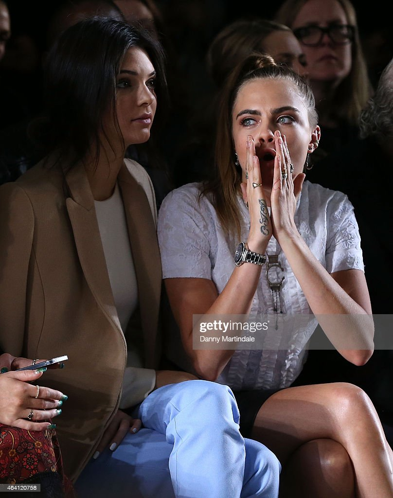 Cara Delevingne and Kendall Jenner watch the TopShop unique show during London Fashion Week Fall/Winter 2015/16 on February 22, 2015 in London, United Kingdom.