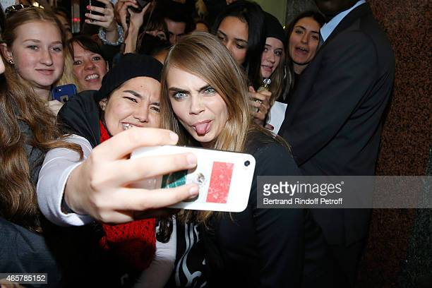 Cara Delevingne poses for photographs with fans as she attends the Yves Saint Laurent Beauty event at Galeries Lafayette on March 10 2015 in Paris...