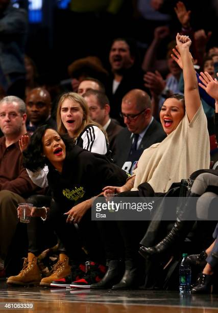 Cara Delevingne Rihanna and Jennifer Rosales celebrate in the second half of the game between the Brooklyn Nets and the Atlanta Hawks at the Barclays...