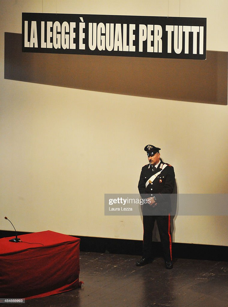 A Carabiniere stands near the sign 'La legge è uguale per tutti' ('The law is equal for everyone') during the hearing in the trial of the Costa Concordia on December 9, 2013 in Grosseto, Italy. Coastguard Captain Gregorio De Falco and Captain Francesco Schettino met for the first time in court today. De Falco, famous for ordering Schettino back onboard after he allegedly abandoned the ship with hundreds of passengers still onboard, took to the stand as a witness. The Costa Concordia capsized on January 13, 2012 leaving 32 people dead.