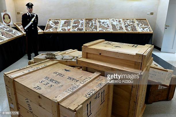 A carabiniere stands next to recovered archaeological artifacts in Rome on March 22 2016 Italian and Swiss art police have busted open an...