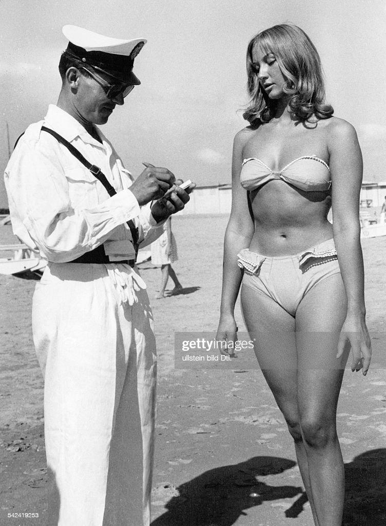 Carabinieri am Strand von Rimini schreibteinen Strafzettel für eine junge Frau mitBikini September 1957