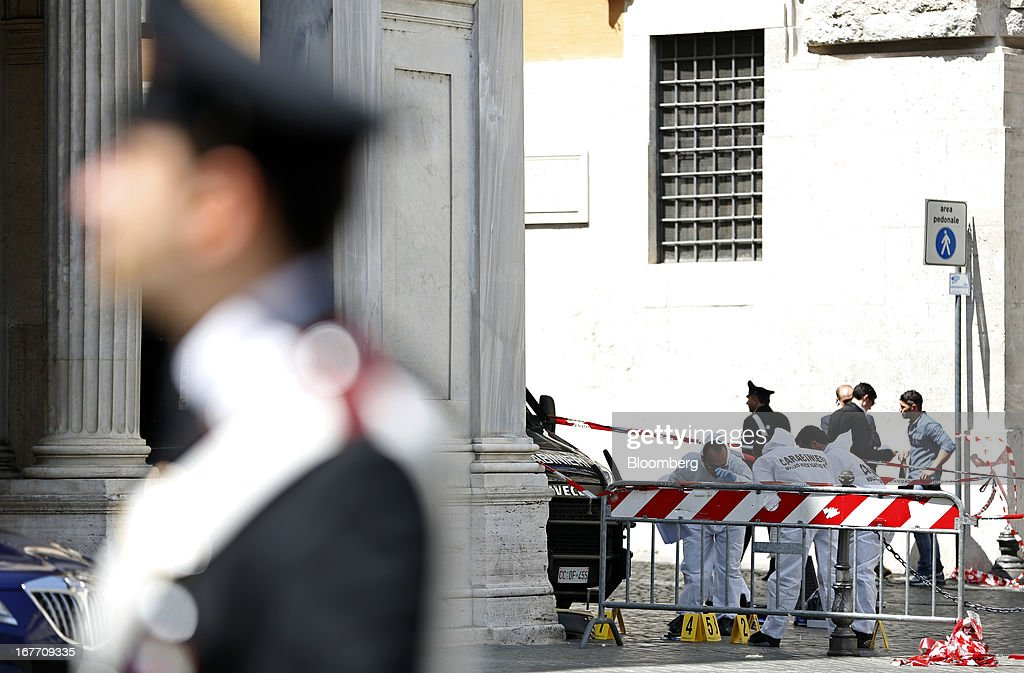 Carabinieri forensics officers look for evidence following a shooting outside the Chigi Palace in Rome, Italy, on Sunday, April 28, 2013. Two Italian police officers were shot outside the prime minister's office in Rome today by a lone gunman while the country's new premier, Enrico Letta, was being sworn in across town, police said. Photographer: Alessia Pierdomenico/Bloomberg via Getty Images