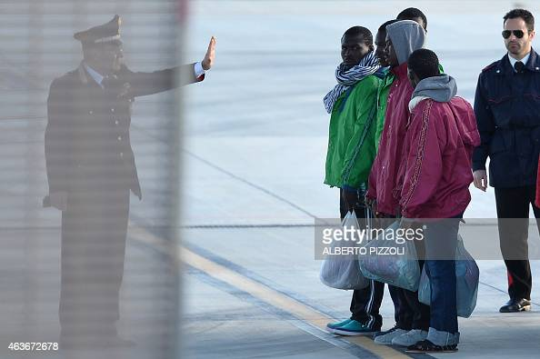 A carabinieri gives instructions to migrants before they board a military plane to be transferred on February 17 2015 at the Lampedusa airport...